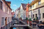 Stadtlandschaft. Schmale alte Straße mit Wasserkanal und Restaurant und Café in Memmingen.