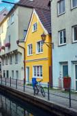Kleines, gelbes Haus in einer engen Straße mit Wasserkanal in der Memminger Altstadt.