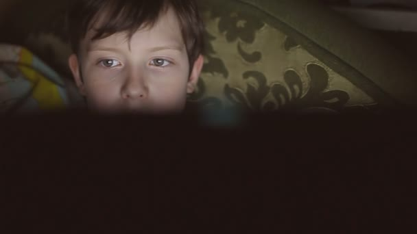 boy teen with laptop computer plays game on Internet indoor