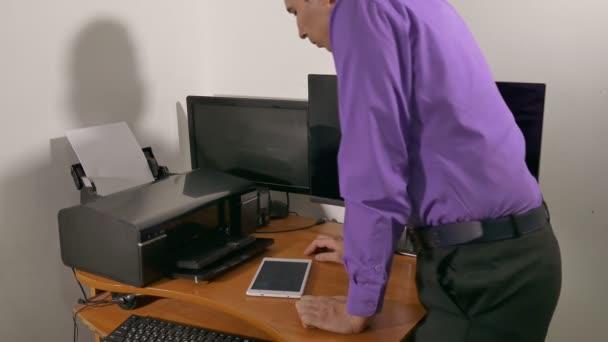 podnikatel v kanceláři tiskne dokumenty na tiskárny