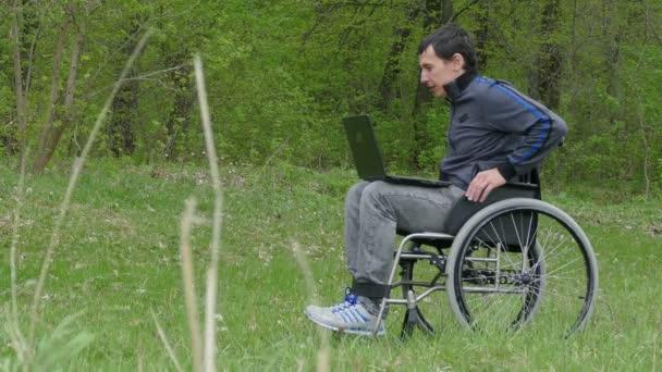 behinderte Mann Video-Chat-Gespräch Rollstuhl mit einem Laptop in einem Rollstuhl arbeiten auf Natur grünen Hintergrund