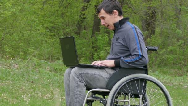 Mann behindert Videochat Gespräch Rollstuhl mit einem Laptop in einem Rollstuhl arbeiten auf Natur grünen Hintergrund