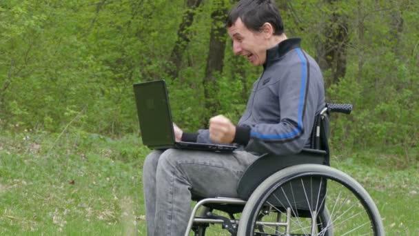 Mann behindert Überraschungserfolg Rollstuhl Sieg mit einem Laptop im Rollstuhl arbeiten auf Natur grünen Hintergrund