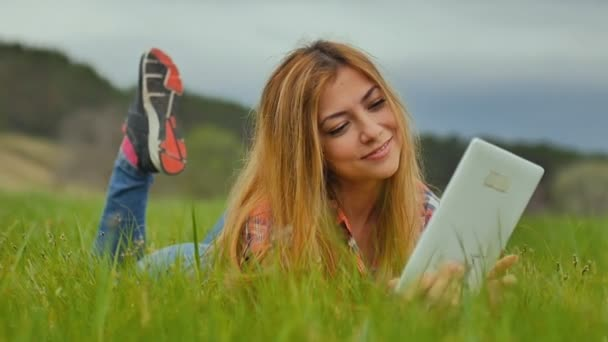 girl sexy with tablet lying on outdoors green grass slow motion