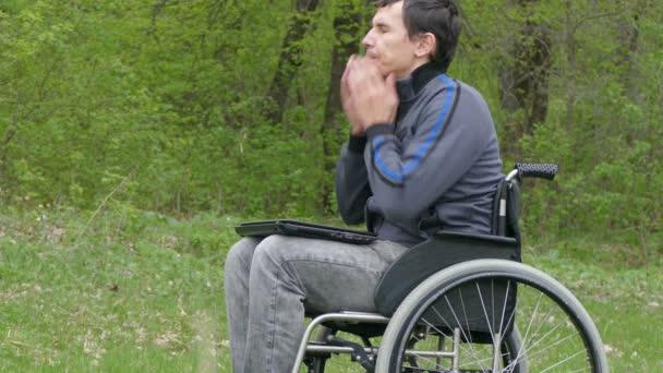 Behinderter denkt müde von Pausenproblemen Rollstuhl mit Laptop im Rollstuhl arbeitet auf naturgrünem Hintergrund