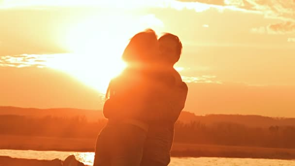 Woman a man turns in his hands at sunset slow motion video
