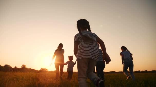 glückliche Familienkinder laufen gemeinsam im Park bei Sonnenuntergang. Menschen im Parkkonzept. glückliche Familie freudigen Lauf. glückliche Familie und kleines Baby Kind Sommer Kind Traum Konzept Spaß