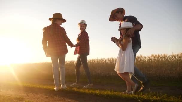 Menschen im Park. glückliche Familiensilhouette Spaziergang bei Sonnenuntergang. Mama, Papa und Töchter gehen Händchen haltend durch den Park. happy family kid dream concept. Eltern und Kinder gehen Silhouettenspaziergang zurück