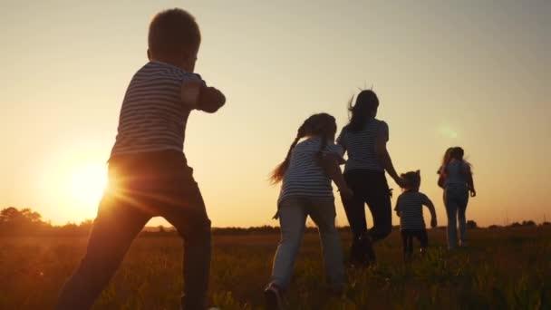 děti šťastné rodinné dítě spolu běhají v parku při západu slunce silueta. lidé v konceptu parku. Matka dcera a syn radostně utíkají. šťastná rodina a malé dítě léto dítě sen zábava koncept