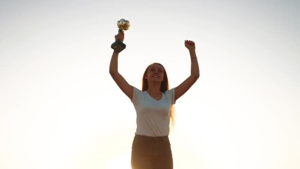 Teenie-Mädchen feiert Sieg Erfolg. Silhouette eines glücklichen Sportlermädchens mit Pokalen in der Hand jubelt. Kindertraum Sieger Konzept. Menschen im Park. Mädchen mit Pokal in der Hand