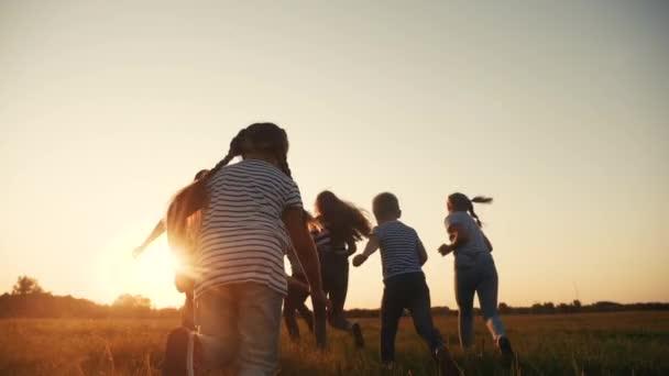 šťastné rodinné děti spolu běhají v parku při západu slunce silueta. lidé v konceptu parku. šťastný rodinný radostný běh. šťastná rodina a malé dítě zábava léto dítě sen koncept