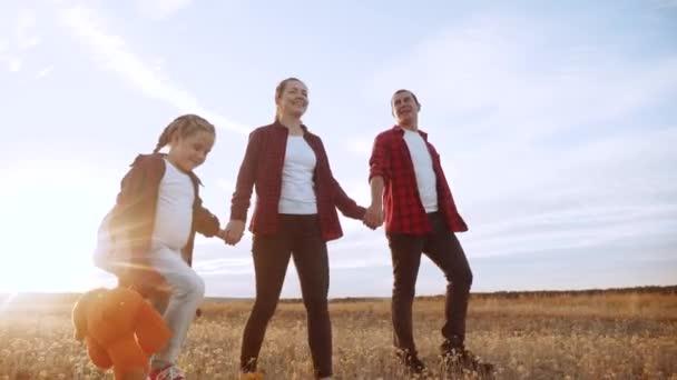 šťastnou rodinnou procházku v parku. přátelské rodinné dítě sen koncept. Máma táta a dítě životní styl dítě procházka v parku na zelené trávě venku. šťastná rodina s jejich zády procházky v parku