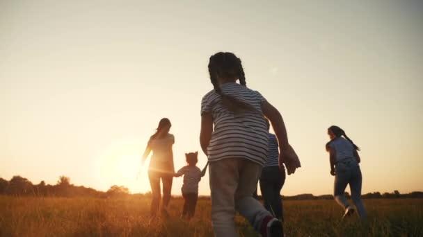 glückliche Familienkinder laufen gemeinsam im Park bei Sonnenuntergang. Menschen im Parkkonzept. glückliche Familie freudigen Lauf. glückliche Familie und kleines Baby Kind Sommer Kind Traum Spaß Konzept