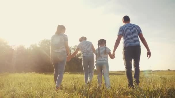 glückliche Familie beim Spaziergang im Park. freundliche Familien-Kind-Traum-Konzept. Mama Papa und Kinder spazieren im Park auf grünem Gras im Freien. Lifestyle glückliche Familie mit dem Rücken zu Fuß im Park in