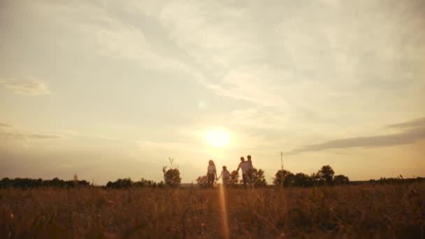šťastné rodinné děti se společně procházejí v parku při západu slunce silueta. lidé v konceptu parku máma táta dcera a sestra radostná procházka životní styl. rodiče a malé dítě zábava léto