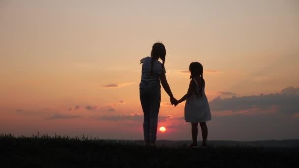 glückliche Familie zwei Schwestern geht bei Sonnenuntergang in der Park-Silhouette. Draußen halten sich zwei Töchter an den Händen. Kindertraum-Konzept. glückliche Familienwanderung zusammen. Sonnenuntergang Kinder kleines Kind zu Fuß im Park