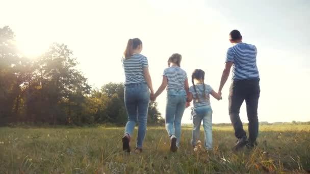 šťastnou rodinnou procházku v parku. přátelské rodinné dítě sen koncept. Máma táta a děti chodí do parku na zelené trávě venku. šťastná rodina se zády procházky v parku v životním stylu
