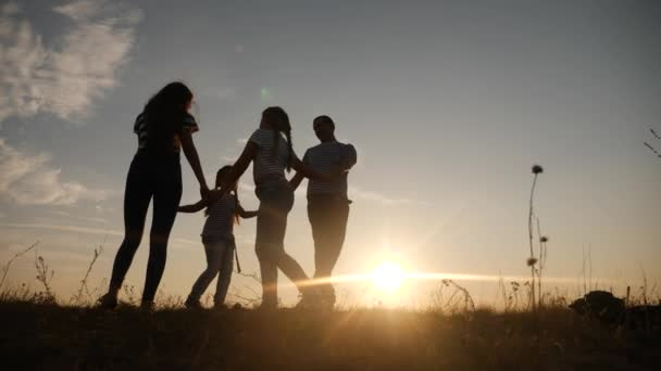 glückliche Familie Mama Papa und Tochter spielen runden Tanz Silhouette bei Sonnenuntergang. Menschen im Park-Kind-Traum-Konzept. glücklich Familie Eltern Spaß mit kleinem Kind Kind Tochter spielen im Park auf Gras Händchen haltend
