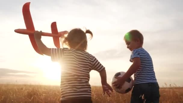 happy kids childs run with an airplane in the park. kid silhouette play plane. happy family dream freedom airplane concept. kids run on wheat field at sunset holds in his hands dream fun toy aircraft