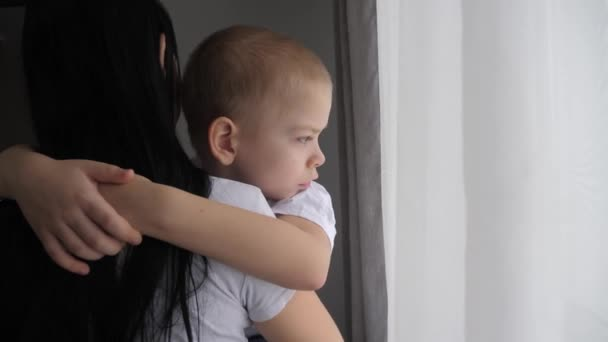 mom holds her son in her arms indoors. happy family concept. mom lifestyle holds a little boy in her arms looking out the window indoors child care happy family