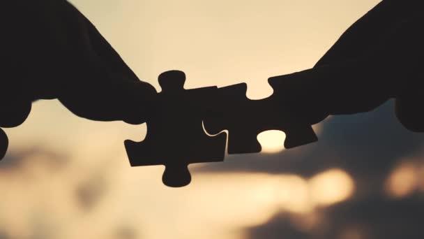Teamwork business finance koncept. životní styl mužské ruce spojují dvě hádanky siluety proti západu slunce. týmová práce symbol asociace a spojení. obchodní strategie partnerství