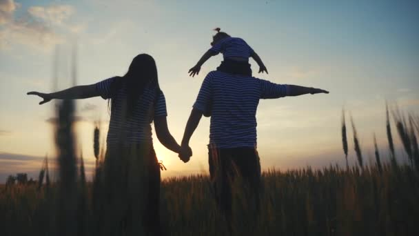 happy family. parents and baby hold hands at sides in the park silhouette. happy family a kid dream concept. dad mom and daughter lifestyle watch the sunset in the park outdoors dream