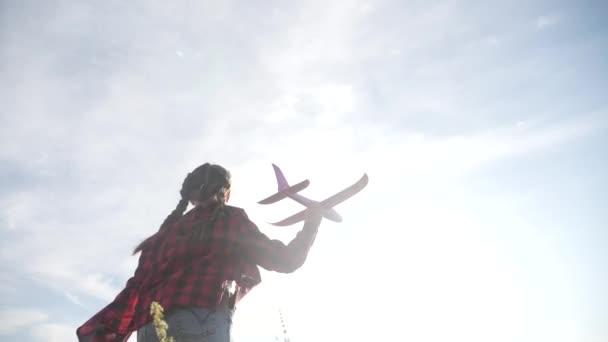 Boldog lány gyerek fut egy repülővel. Kölyök sziluett játszani sík. boldog családi álom szabadság repülőgép koncepció. lánya gyerek fut a búzamezőn naplementekor tartja szórakoztató a kezét álom játék repülőgép