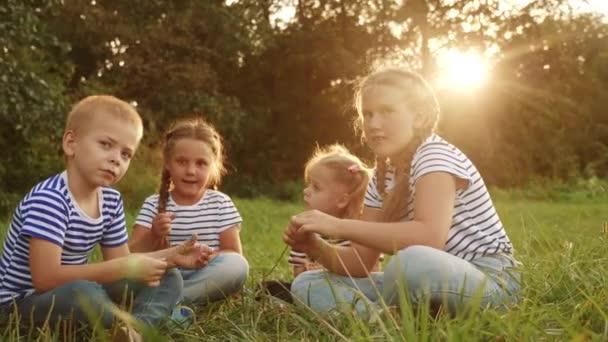 skupina dětí sedí v parku na trávě a povídají si. dítě snít šťastný rodinný koncept. skupina dětí, které odpočívají v parku a baví se povídáním si se šťastnou rodinou. lidé v parku
