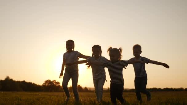 šťastné rodinné děti spolu běhají v parku při západu slunce silueta. lidé v konceptu parku. šťastný zábavný rodinný radostný běh. šťastná rodina a malé dítě léto dítě sen koncept
