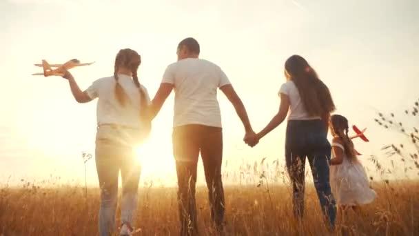 lidi v parku. šťastná rodinná silueta procházka s letadýlkem. Máma táta a dcery chodí v parku a drží se za ruce. koncepce snů šťastných rodinných dětí. rodiče a dítě kráčející zpět silueta letadlo
