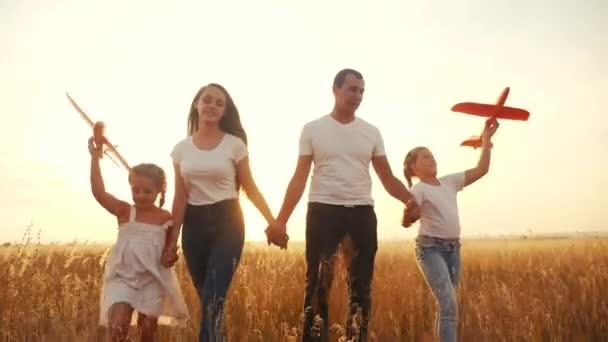 Menschen im Park. glückliche Familiensilhouette Spaziergang mit einem Spielzeugflugzeug. Mutter und Tochter gehen händchenhaltend in den Park. happy family kid dream concept. Eltern und Kind gehen zurück Silhouette