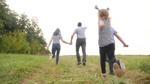 šťastné rodinné děti spolu běhají v parku při západu slunce silueta. lidé v parku koncept máma táta dcera a syn radostný běh. šťastná rodina a malá zábava dítě léto dítě sen koncept