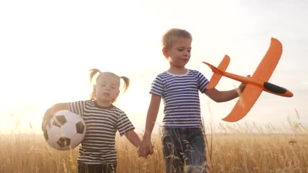 happy kids childs walk with airplane a in the park. kid silhouette play plane. happy family dream freedom airplane concept. kids walk on wheat field at sunset holds fun in his hands dream toy aircraft