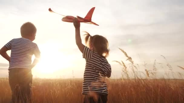 happy kids childs run with an airplane in the park. kid silhouette play plane. happy family dream freedom airplane concept. kids run on wheat field fun at sunset holds in his hands dream toy aircraft