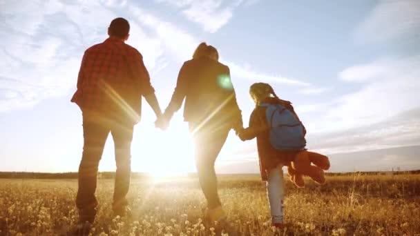 šťastnou rodinnou procházku v parku. přátelské rodinné dítě sen koncept. Máma táta a dítě procházka v parku na zelené životní styl trávy venku. šťastná rodina s jejich zády procházky v parku