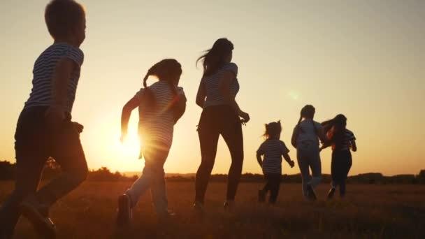 Kinder glücklich Familie Kind zusammen laufen im Park bei Sonnenuntergang Silhouette. Menschen im Parkkonzept. Mutter Tochter und Sohn fröhlich laufen. Spaß glückliche Familie und kleine Baby Kind Sommer Kind Traum-Konzept