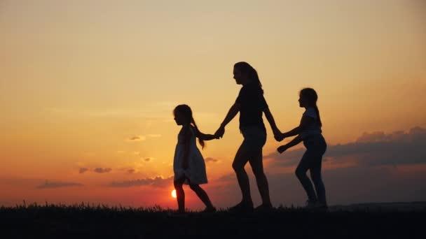 glückliche Familienspaziergänge bei Sonnenuntergang in der Park-Silhouette. Mutter und zwei Töchter halten sich draußen an den Händen. Kindertraum-Konzept. glückliche Familienwanderung zusammen. Lifestyle Mutter und kleine Kinder spazieren im Park