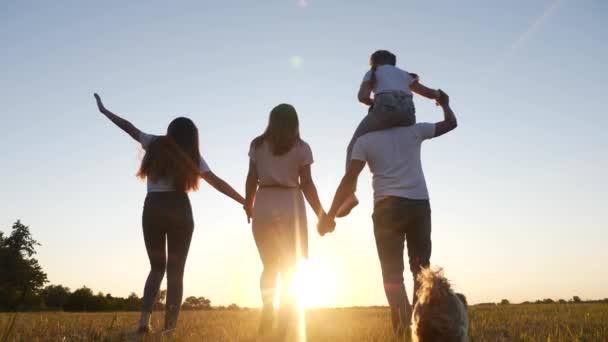 lidi v parku. šťastná rodinná silueta při západu slunce. Máma táta a dcery chodí v parku a drží se za ruce. Happy lifestyle rodina dítě sen koncept. rodiče a děti kráčející zpět silueta