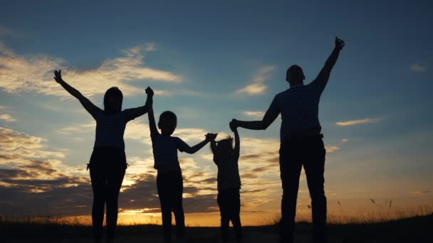 happy family raise their hands up in the park silhouette. family friendly kid dream concept. happy family parents holding hands raised their hands up. dad mom dream daughter and son are happy in park