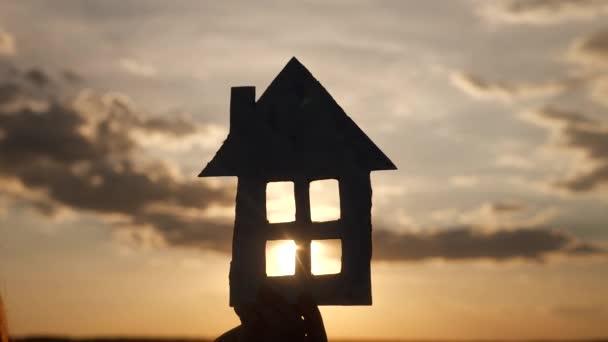 Papierhaus in der Hand Silhouette bei Sonnenuntergang. Versicherungshypothek Eigenheimmarkt Konzept. Büttenpapier Haus in der Sonne Lifestyle bei Sonnenuntergang Silhouette. Traum vom Eigenheim als Symbol