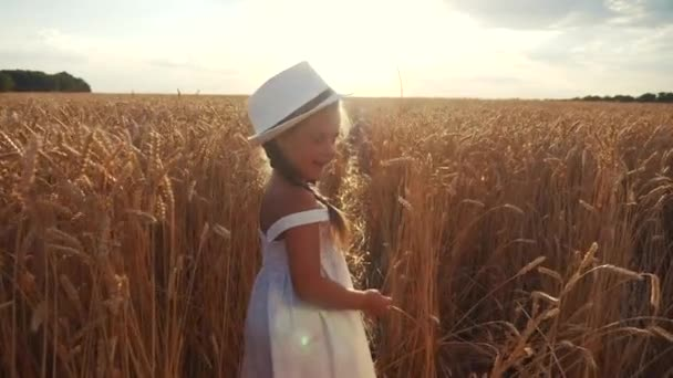 kid little girl walking on a wheat field. happy childhood dream family concept. baby daughter in a white hat and dress walks through a wheat field view from the back. lifestyle agriculture harvesting