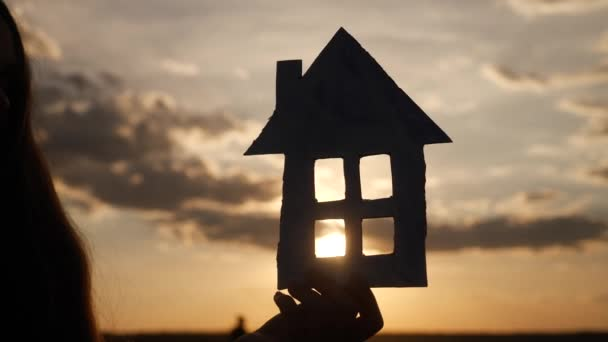papírový dům v ruce silueta při západu slunce. koncepce pojistného hypotečního trhu. ručně vyrobený papírový dům na slunci při západu slunce silueta. sen o domácí akumulace symbol životního stylu