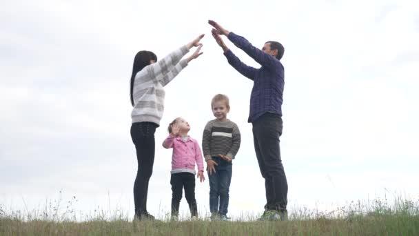 glückliche Familie. Teamwork erwachsene Eltern und kleine Kinder zeigt ein Haus und ein Komfortsymbol. glückliche Familie Mama Papa und Kinder zeigen ein Haus Lifestyle Dach halten die Hände über dem Kopf
