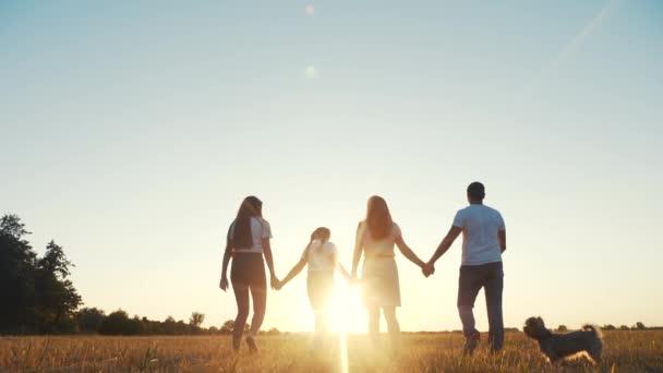 lidi v parku. šťastná rodinná silueta při západu slunce. Máma táta a dcery chodí v parku a drží se za ruce. koncepce snů šťastných rodinných dětí. rodiče a děti kráčející zpět silueta životní styl