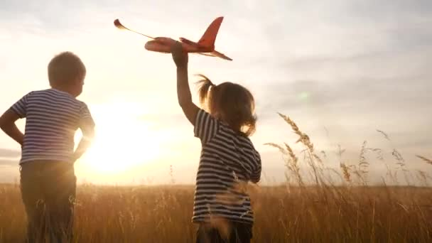happy kids childs run with an airplane in the park. kid silhouette play plane. happy family dream freedom airplane concept. kids run on wheat field at sunset fun holds in his hands dream toy aircraft