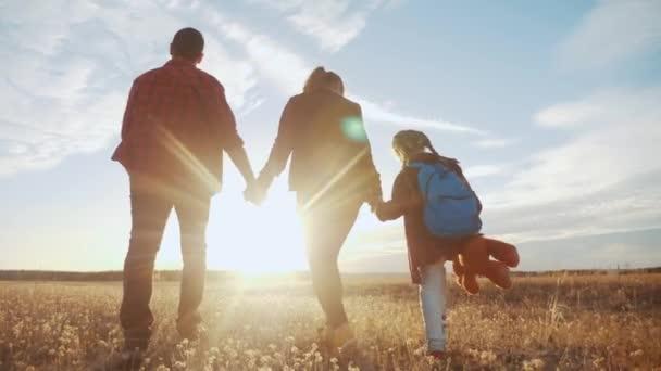 glückliche Familie beim Spaziergang im Park. freundliche Familien-Kind-Traum-Konzept. Mama Papa und Kind Kind spazieren im Park auf grünem Gras im Freien. glückliche Familie mit dem Rücken im Park