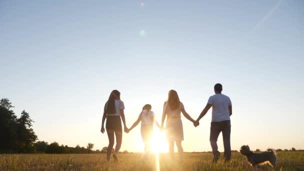 lidi v parku. šťastná rodinná silueta při západu slunce. Máma táta a dcery chodí v parku a drží se za ruce. koncepce snů šťastných rodinných dětí. rodiče a děti kráčející životní styl zpět silueta