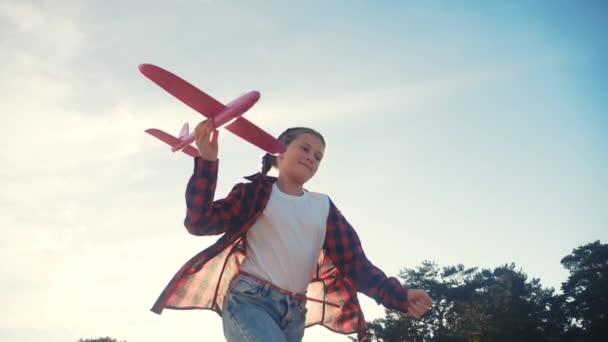 Boldog lány gyerek fut egy repülővel. Kölyök sziluett játszani szórakoztató repülőgép. boldog családi álom szabadság repülőgép koncepció. lánya gyerek fut a búzamezőn naplementekor tartja a kezében álom játék repülőgép