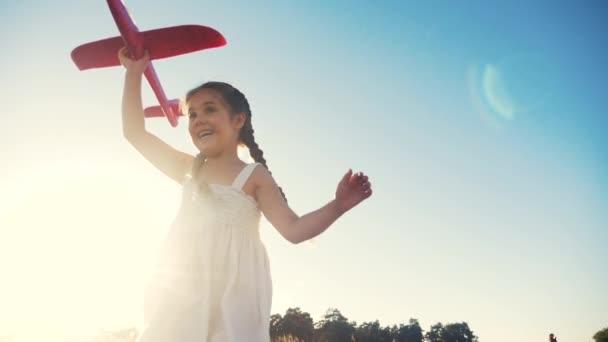 Boldog lány gyerek fut egy repülővel. Kölyök sziluett játszani sík. boldog családi álom szabadság repülőgép koncepció. lánya gyerek fut a búzamezőn naplementekor tartja a kezében álom repülőgép szórakoztató játék