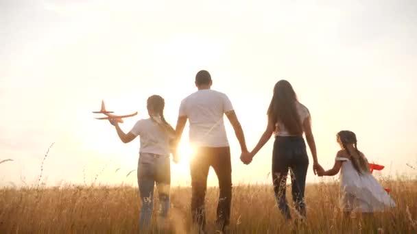 Menschen im Park. glückliche Familiensilhouette Spaziergang mit einem Spielzeugflugzeug. Mama, Papa und Töchter gehen Händchen haltend durch den Park. happy family kid dream concept. Eltern Flugzeug und Kind zu Fuß zurück Silhouette